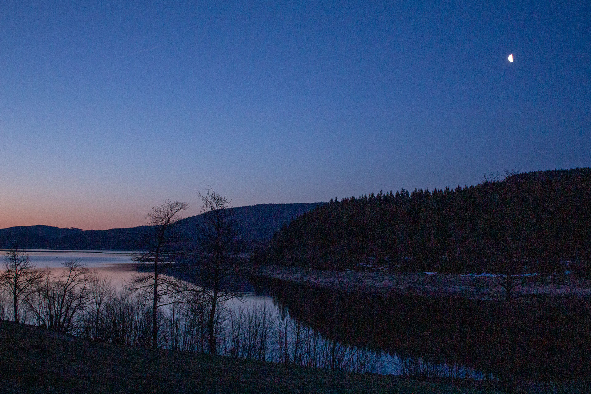 Noch steht der Mond am blauen Nachthimmel.
